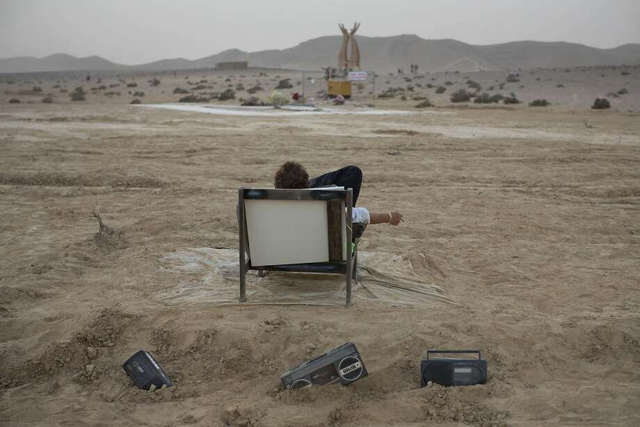 In this photo taken Wednesday, June 4, 2014, an Israeli man rests on a couch during Israel's first Midburn festival, modeled after the popular Burning Man festival held annually in the Black Rock Desert of Nevada, in the desert near the Israeli kibbutz of Sde Boker. Some 3,000 people set up a colorful encampment in the dusty moonscape, swinging from hoops by day and burning giant wooden sculptures by night.  Photo: Oded Balilty, Associated Press