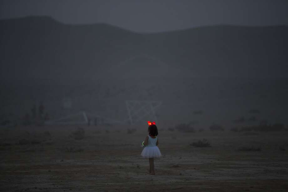 In this photo taken Wednesday, June 4, 2014, a young Israeli girl walks in the playa during Israel's first Midburn festival, modeled after the popular Burning Man festival held annually in the Black Rock Desert of Nevada, in the desert near the Israeli kibbutz of Sde Boker. Some came costumed in cape or corset. Others, from babies to grandparents, went nude. Participants brought their own food and water, and shared with others. The only thing on sale was ice because of the scorching heat.  Photo: Oded Balilty, Associated Press