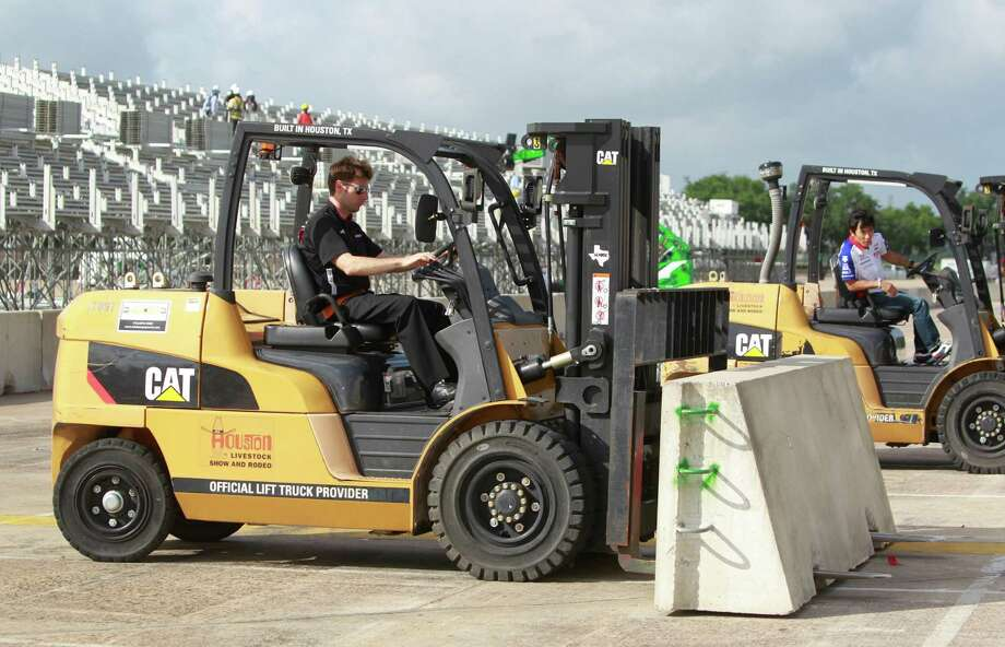IndyCar drivers Will Power, left, and Takuma Sato, right, move concrete barriers with fork lifts during a Grand Prix of Houston media event at NRG Park Monday, June 9, 2014, in Houston. Photo: Melissa Phillip, Houston Chronicle / © 2014  Houston Chronicle