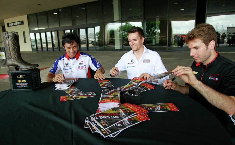 The A.J. Foyt Grand Prix of Houston trophy is shown on the left as IndyCar drivers Takuma Sato, left, Mikhail Aleshin, center, and Will Power, right, sign autographs during a Grand Prix of Houston media event at NRG Park Monday, June 9, 2014, in Houston. Photo: Melissa Phillip, Houston Chronicle / © 2014  Houston Chronicle