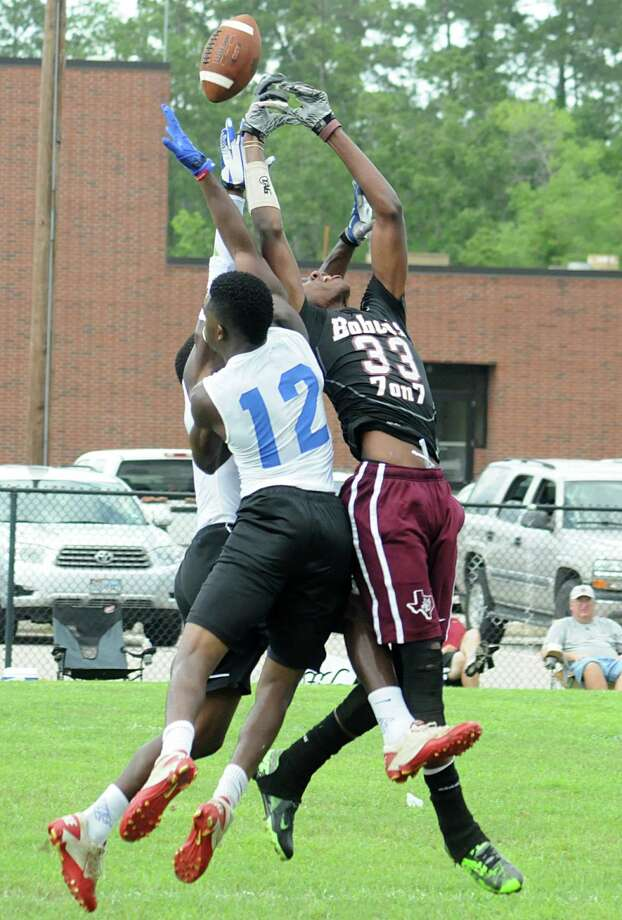 Cypress Fairbank's Broderick Chambers has the ball knocked loose by Oak Ridge defenders during the 7 on 7 state qualifying football tournament at The Woodlands High School.  Photo: David Hopper, For The Chronicle / freelance