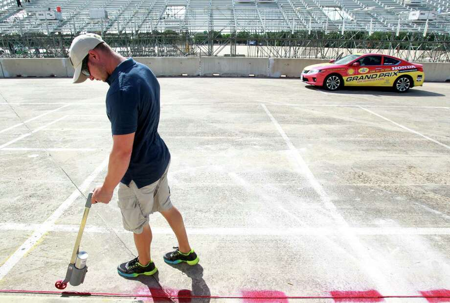 Joe Marias with Great Lakes Reloading paints a line for a race wall during preparations for the Grand Prix of Houston at NRG Park Monday, June 9, 2014, in Houston. Photo: Melissa Phillip, Houston Chronicle / © 2014  Houston Chronicle
