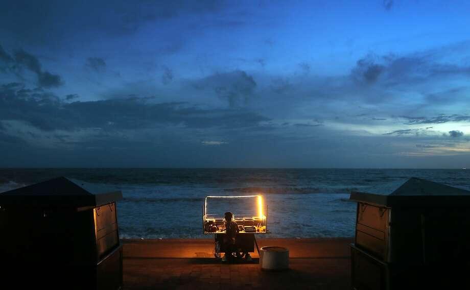 When monsoon season begins,the tourists leave, making this seaside promenade snack vendor a lonely fellow in Colombo, Sri Lanka. Photo: Eranga Jayawardena, Associated Press