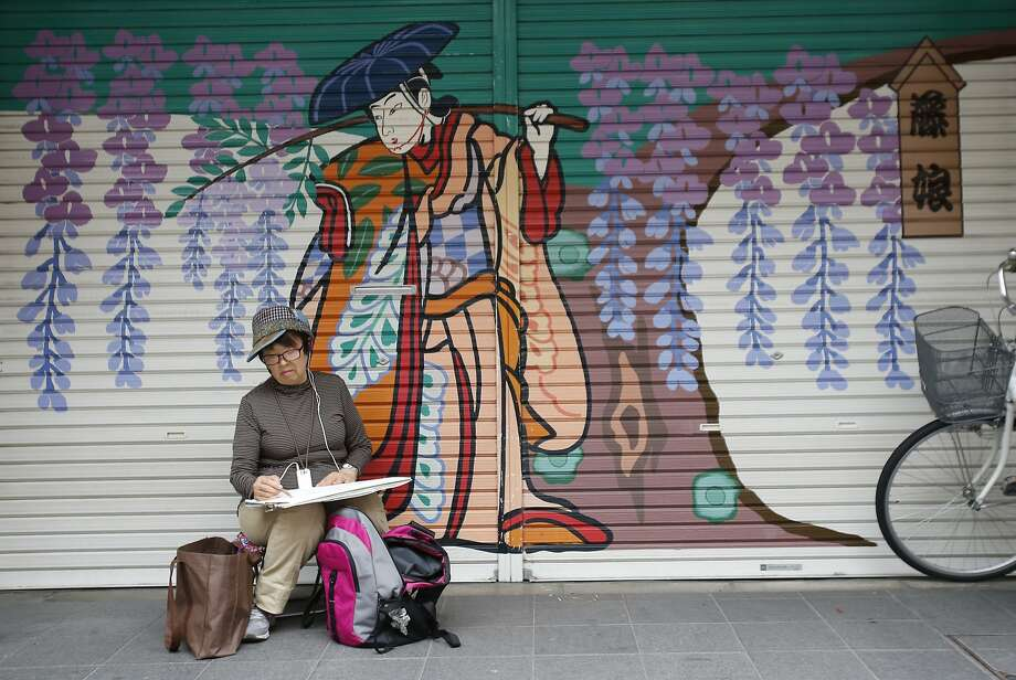 I can't work with you looking over my shoulder:A sketch artist draws in front of a closed restaurant in Tokyo. Photo: Shizuo Kambayashi, Associated Press