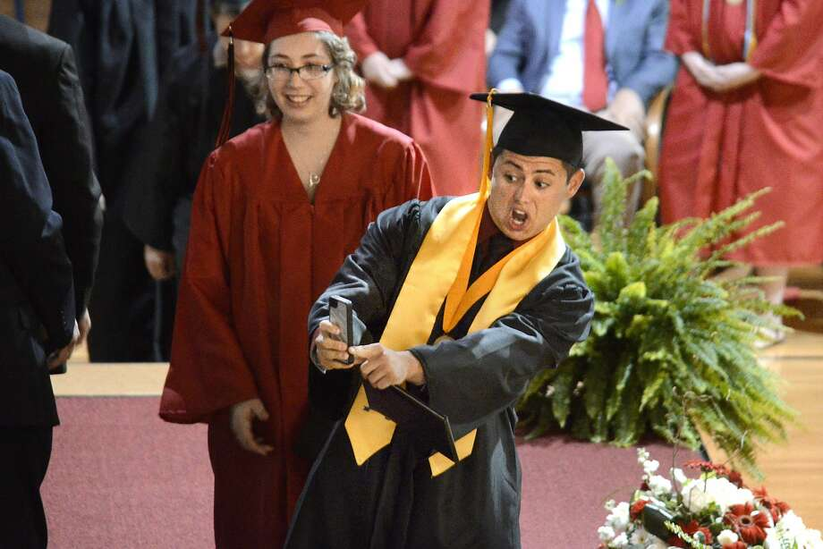 Pomp and selfie: Diploma in one hand and phone in the other, Bryce Moore documents his graduation from Eastbrook High School for posterity near Marion, Ind. Photo: Jeff Morehead, Associated Press