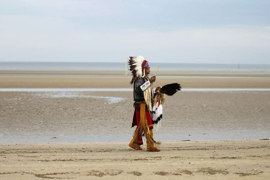 A descendant of Comanche soldiersprays on Utah Beach in Sainte-Marie-du-Mont, France. Fourteen Comanche code talkers landed June 6, 1944, on the beach with the 4th U.S. Infantry Division. They transmitted messages in Comanche to thwart any Germans intercepting dispatches. Photo: Charly Triballeau, AFP/Getty Images