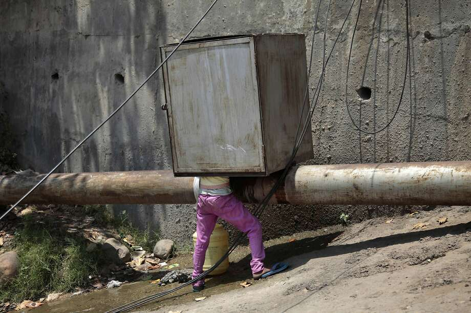 Water scarcity in India: A boy climbs under a metal shed to collect drinking water from a leaking pipeline in the outskirts of Jammu. Photo: Channi Anand, Associated Press