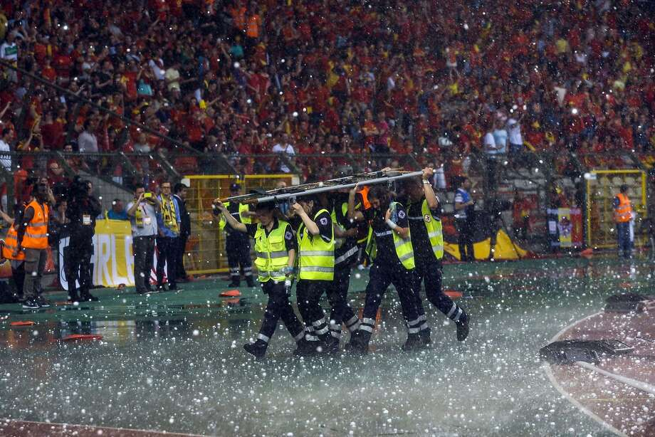 Another use for the stretcher: Red Cross members use a stretcher to protect themselves from hailstones raining down during a friendly football match between Belgium and Tunisia in Brussels. Photo: Thierry Roge, AFP/Getty Images