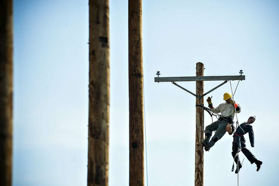 Saving the 'hurt man':Richard Sanspree climbs a telephone pole to rescue a dummy while competing in the Warren Rural Electric Cooperative Corporation's Tennessee Valley Lineman Rodeo in Bowling Green, Ky. Photo: Miranda Pederson, Associated Press