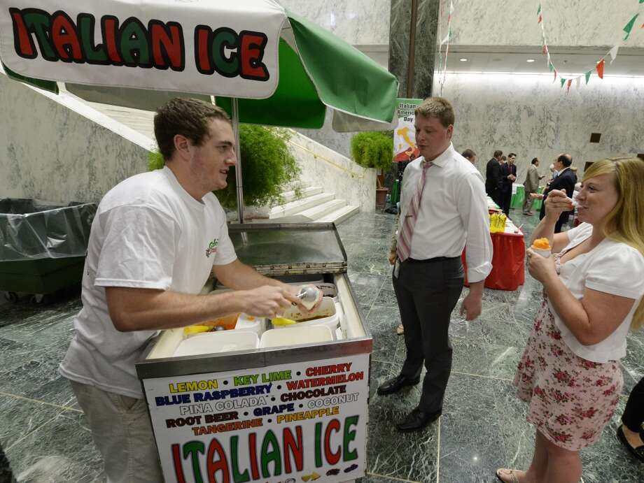Steven Sleasman, 20 of Colonie and representing Guido's Frozen Deserts, hands out free Italian ices during an Italian fest Monday afternoon June 9, 2014 in the Legislative Office Building in Albany, N.Y.      (Skip Dickstein / Times Union) Photo: SKIP DICKSTEIN, ALBANY TIMES UNION