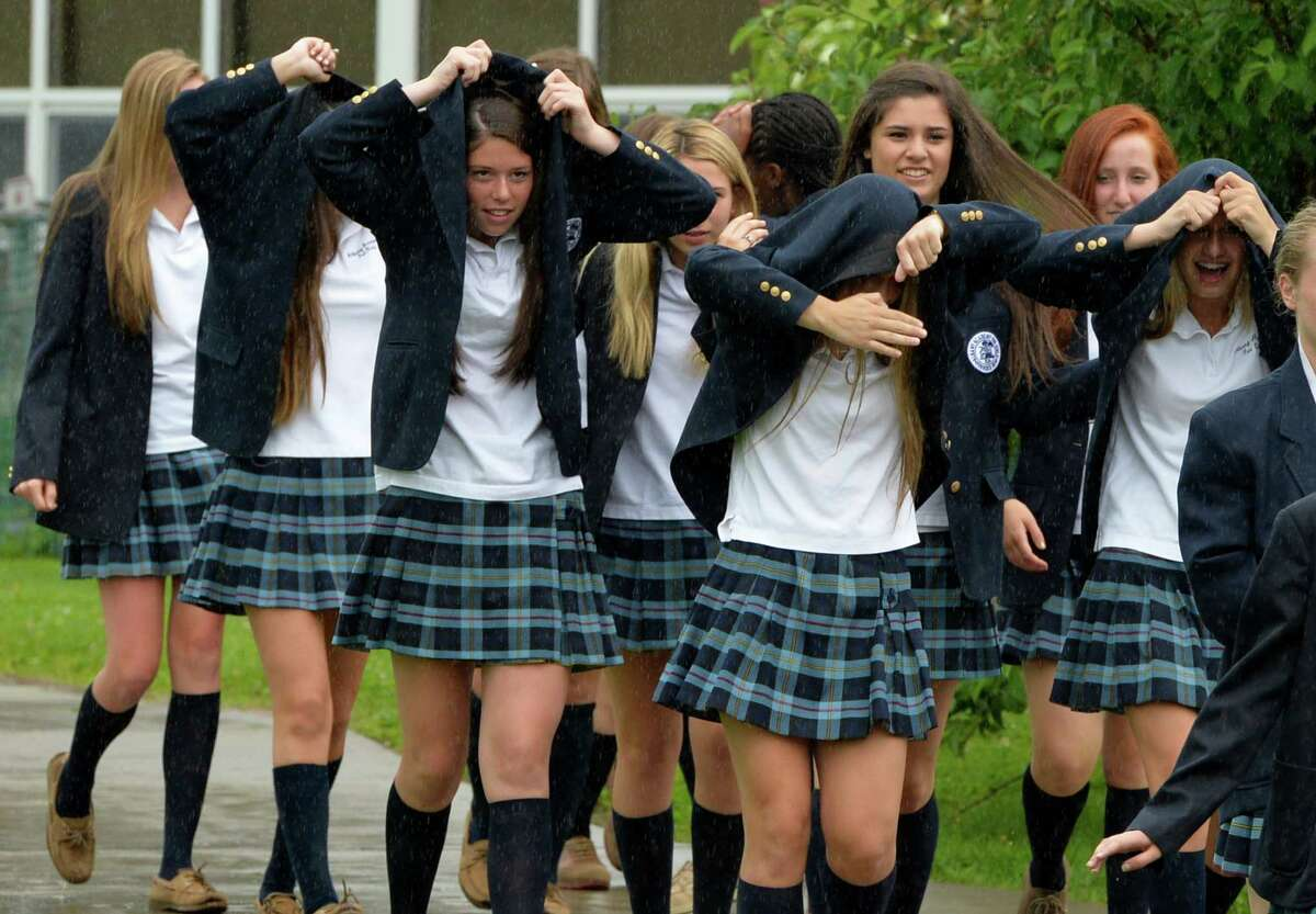 Members of the Albany Academy for Girls Class of 2017 hold their uniform jackets over their heads to protect them from the rain as they arrive for the Academy's 200th commencement exercise Monday morning, June 9, 2014, at the Albany Academy for Girls in Albany, N.Y. (Skip Dickstein / Times Union)