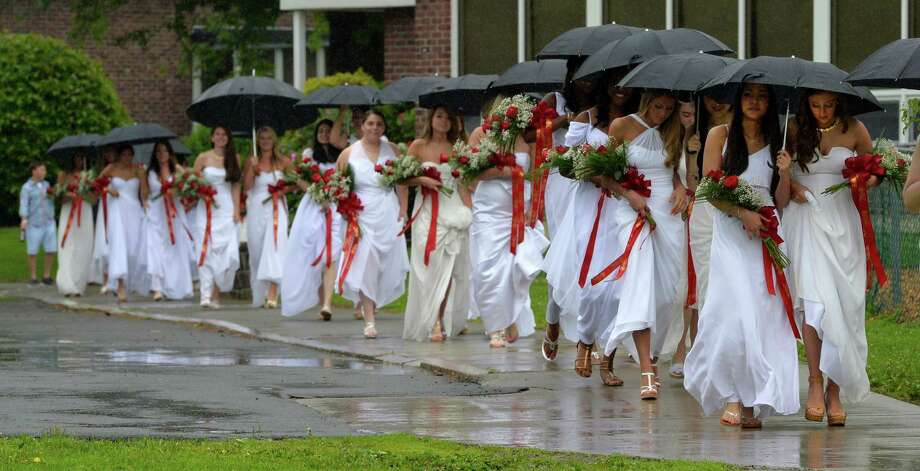 Members of the Albany Academy for Girls graduating class of 2014 are covered by  umbrellas as they arrive for the Academy's 200th commencement exercise Monday morning, June 9, 2014, at the Albany Academy for Girls in Albany, N.Y. (Skip Dickstein / Times Union) Photo: SKIP DICKSTEIN / 00027200A