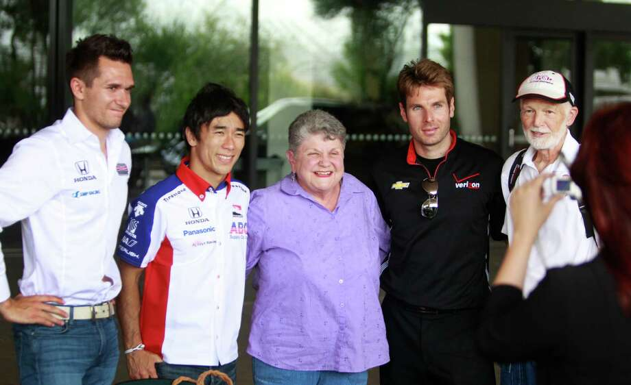 IndyCar drivers Mikhail Aleshin, left, Takuma Sato, and Will Power, second from right, pose with fans Linda Smith, center, and her husband, Bob Smith, right, of Spring during a Grand Prix of Houston event at NRG Park Monday, June 9, 2014, in Houston. The couple were among a few fans who were selected to come to the event for autographs and photos with the drivers. Photo: Melissa Phillip, Houston Chronicle / © 2014  Houston Chronicle