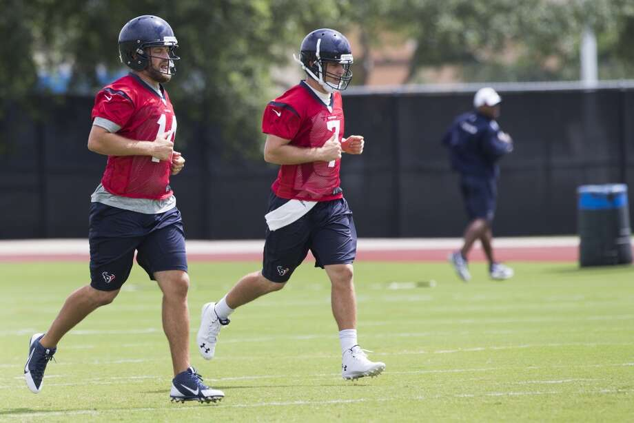 Texans quarterbacks Ryan Fitzpatrick, left, and Case Keenum jog across the field. Photo: Brett Coomer, Houston Chronicle