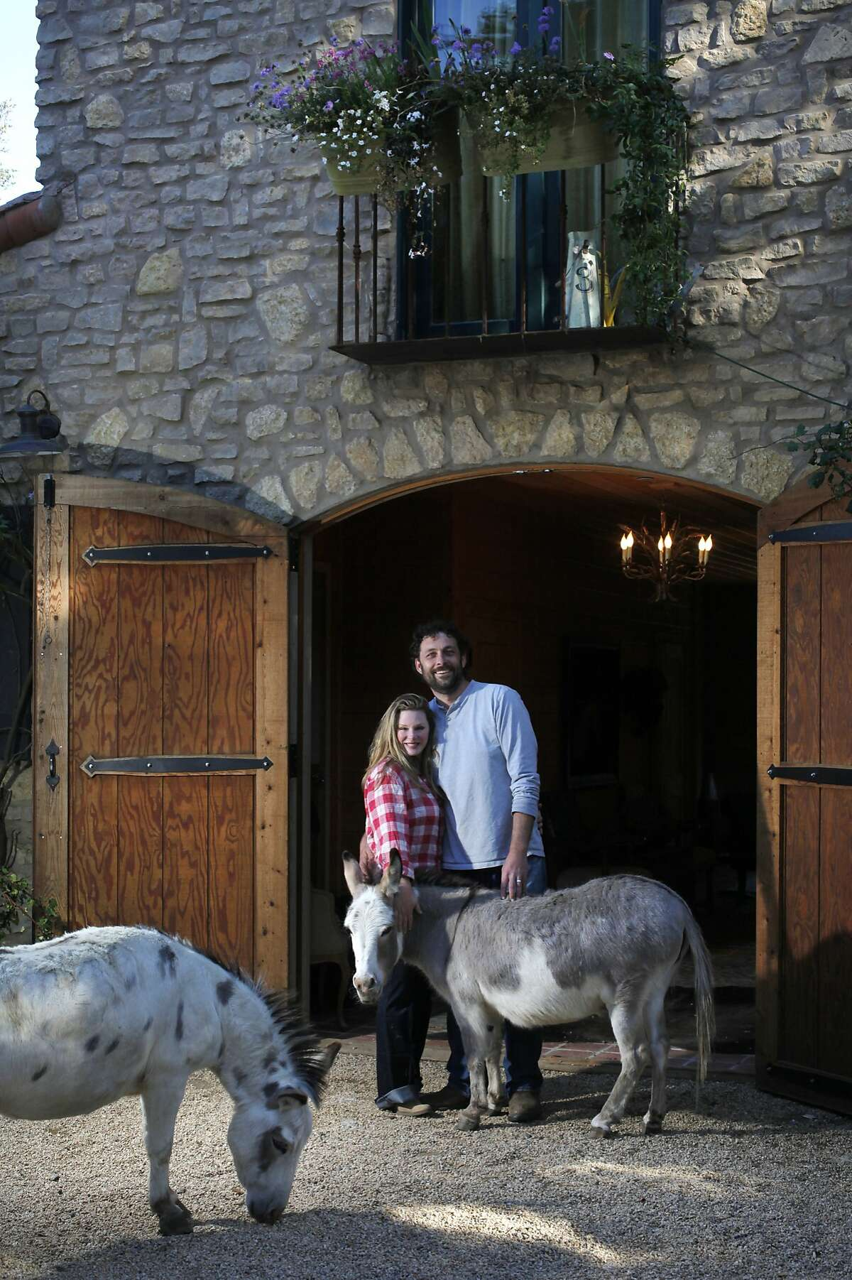Heather Gillette, 44, and her husband Christopher Carstens, 34, pictured with miniature donkeys Large Marge, left, and Penelope May 22, 2014 in front of their home in Woodside, Calif. The couple bought the land in 2006 and built the barn with horse stables with the intent of living in the upstairs space. Over the years, though, Heather took over the downstairs area. Sometimes animals from their land wander in and out of their home, including ducks, a chicken, three dogs, cats and the occasional horse.