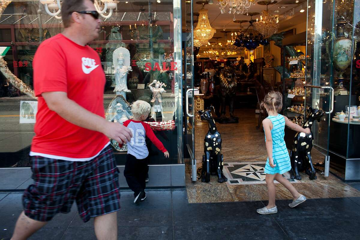 People pass statues in front of Majestic Collection Art Gallery in San Francisco, Calif. on Monday, June 9, 2014. A two-year old boy was killed Friday when he climbed a statue in front of the store. The store had been warned to keep the statues behind the blue lines on the sidewalk.