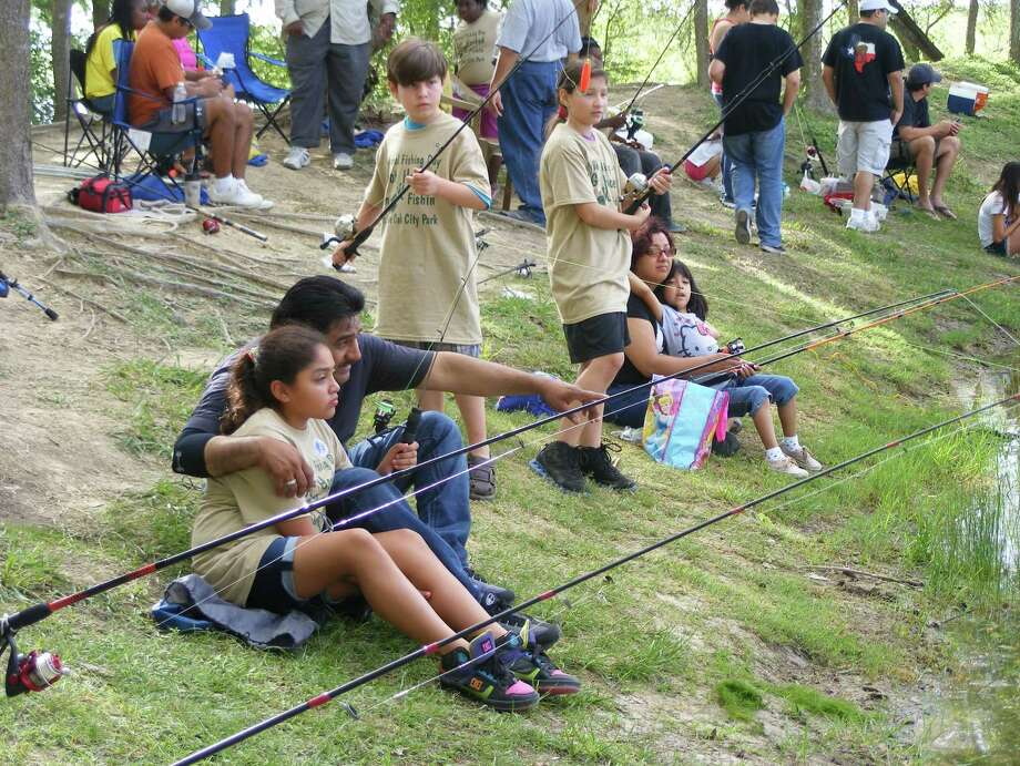 Universal City resident Jerry Castro, seated, points to the bobber on his daughter Veronica's fishing line. The two were among the hundreds who turned out Saturday for the annual Live Oak Junior Fishing Day at Live Oak Park. Photo: Jeff B. Flinn / Northeast Herald