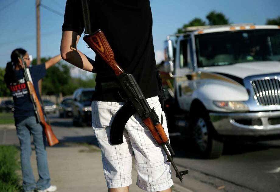 "FILE - In this May 29, 2014, file photo, Kory Watkins, front, coordinator for Open Carry Tarrant County, carries his Romanian AK 47 over his shoulder as he and his wife Janie, rear, along with others, gather for a demonstration in Haltom City, Texas. Companies, customers and others critical of Texas gun rights advocates who have brought military-style assault rifles into businesses as part of demonstrations supporting ""open carry"" gun rights now have a surprising ally: the National Rifle Association. The NRA has long been a zealous advocate for gun owners' rights. But the group's lobbying arm, the Institute for Legislative Action, has called the demonstrations counterproductive to promoting gun rights, scary and ""downright weird.""  (AP Photo/Tony Gutierrez, File) Photo: Tony Gutierrez, Associated Press / AP"
