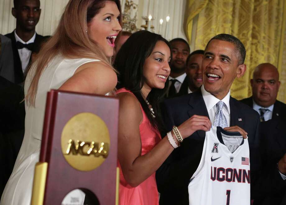 U.S. President Barack Obama (R) receives a jersey from point guard Bria Hartley (2nd L) and center Stefanie Dolson (L) of the University of Connecticut women's basketball team during an East Room event at the White House June 9, 2014 in Washington, DC. President Obama hosted the NCAA Champion UConn Huskies Men's and Women's Basketball teams to honor the teams and their 2014 NCAA Championships. Photo: Alex Wong, Alex Wong/Getty Images / 2014 Getty Images Connecticut Post contributed