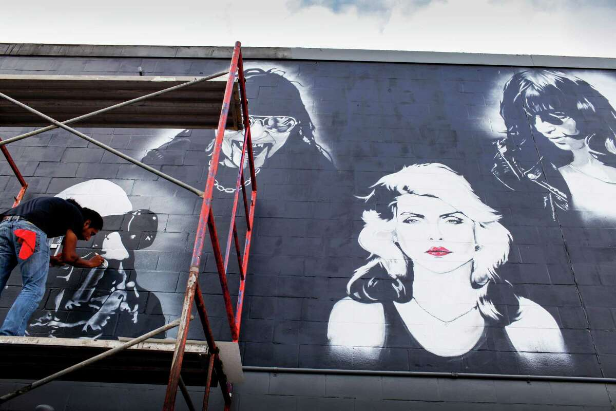 Rene Fernandez paints the west wall of Numbers Nightclub, June 5, 2014 in Houston. Fernandez says each portrait takes about two hours. Fernandez is a regular at the nightclub, and the musicians pictured represent the music played on Fridays, Classic Numbers night. The full line up of musicians in the mural are Trent Renzor, left, of Nine Inch Nails, Al Jourgensen of Ministry, Blondie, Joey Ramone, David Bowie, Ian Curtis of Joy Division, Morrissey, Siouxsie Sioux of Siouxsie and the Banshees, and Robert Smith of The Cure. Fernandez is creating the mural for free. (Eric Kayne/For the Chronicle)