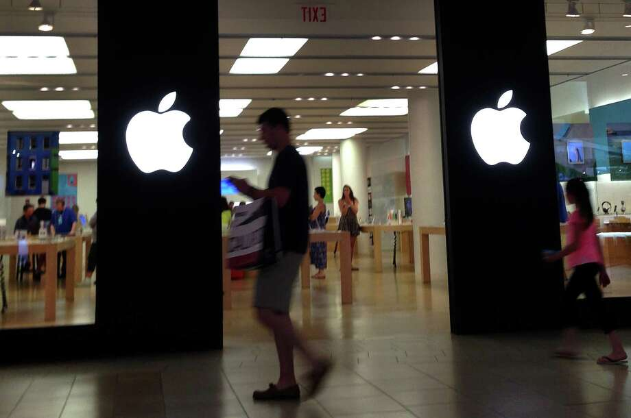 A shopper walks by an Apple store in Peabody, Mass., Monday, June 9, 2014. Apple's resurgent stock may have as much to do with financial engineering as the company's technological wizardry. In late April, the iPhone and iPad maker announced plans to split its stock for the first time in nine years. Since then, Apple's stock has climbed 23 percent, creating more than $100 billion in shareholder wealth while the Standard & Poor's 500 edged up just 4 percent. (AP Photo/Elise Amendola) ORG XMIT: MAEA107 Photo: Elise Amendola / AP