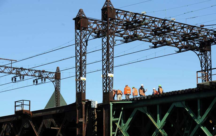 Metro-North workers repair the railroad swing bridge over the Norwalk River in Norwalk, Conn. on Thursday, May 29, 2014. The Walk Bridge failed to close just after 4 a.m., causing major delays on the railroad and on the highways in Connecticut.Trains were stopped at various points and limited shuttle buses ran between East Norwalk and South Norwalk. Eastbound service from Stamford was suspended, while only limited westbound trains were available from South Norwalk. The repairs were completed and service resumed just before 9 a.m. Photo: Cathy Zuraw / Connecticut Post