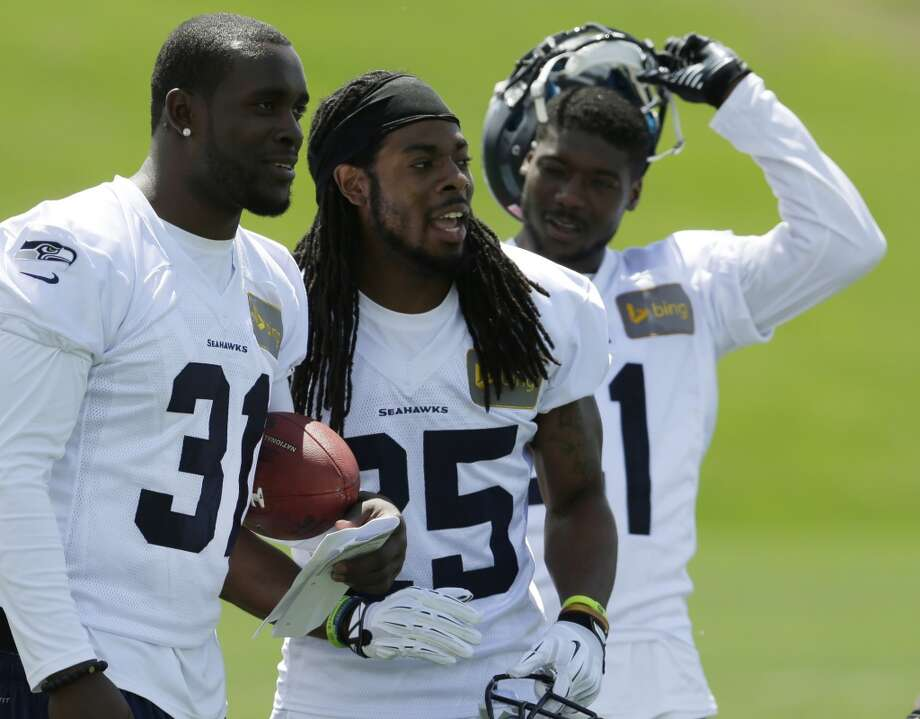 Seattle Seahawks cornerback Richard Sherman (25) stands with strong safety Kam Chancellor, left, and cornerback Byron Maxwell, right, during Seahawks OTAs on Monday. Photo: Ted S. Warren, Associated Press