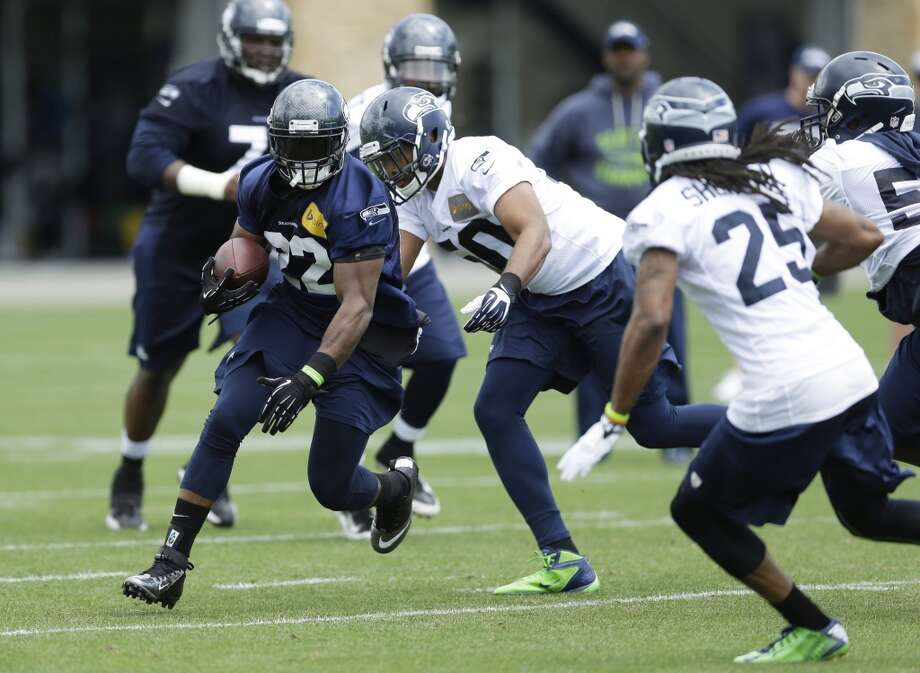 Seattle Seahawks running back Robert Turbin, left, runs the ball during a practice drill at Seahawks OTAs on Monday. Photo: Ted S. Warren, Associated Press