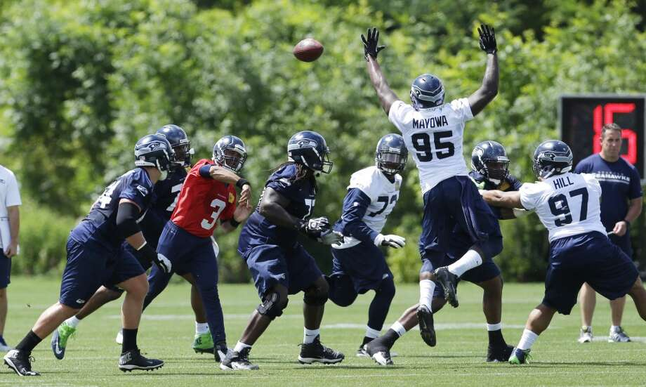 Seattle Seahawks quarterback Russell Wilson (3) passes around the leaping defense of Seattle Seahawks defensive end Benson Mayowa (95) during Seahawks OTAs on Monday. Photo: Ted S. Warren, Associated Press