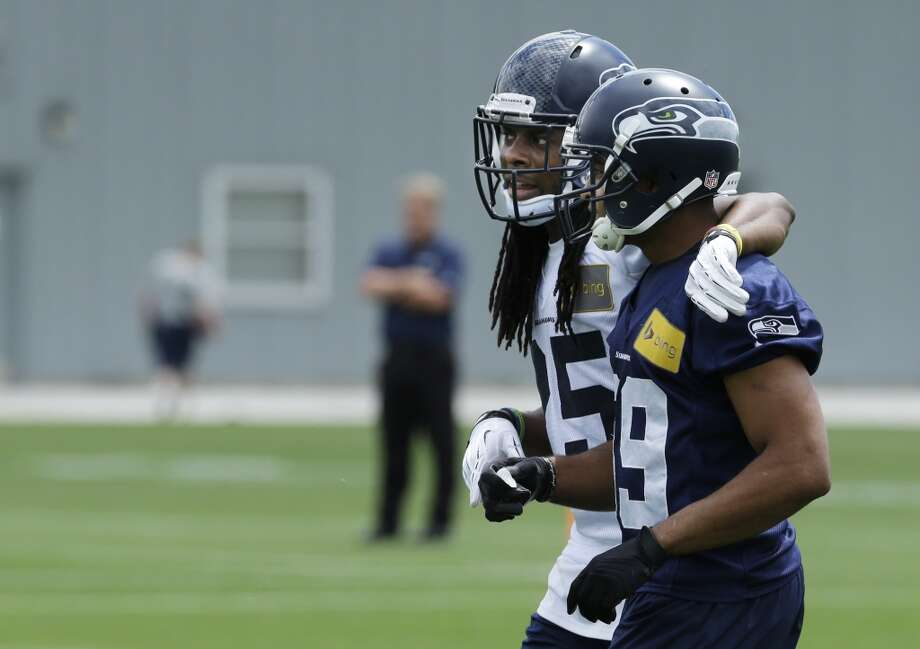 Seattle Seahawks cornerback Richard Sherman, left, walks with wide receiver Doug Baldwin, right, after a play during Seahawks OTAs on Monday. Photo: Ted S. Warren, Associated Press