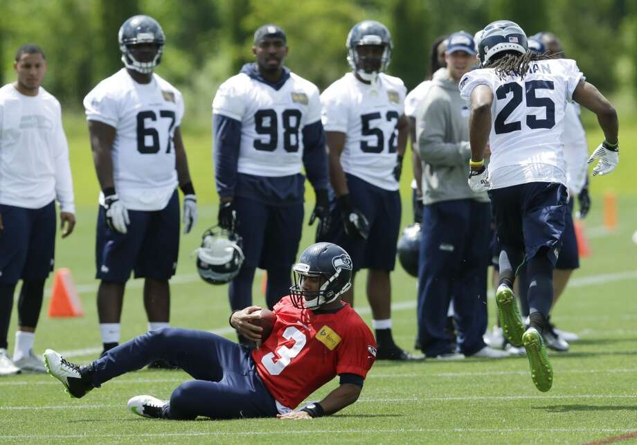 Seattle Seahawks quarterback Russell Wilson (3) slides to avoid Seahawks cornerback Richard Sherman (25) during Seahawks OTAs on Monday. Photo: Ted S. Warren, Associated Press