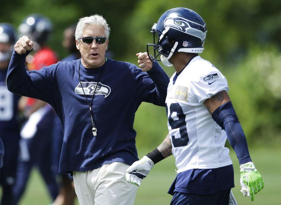 Seattle Seahawks head coach Pete Carroll, left, gestures to free safety Earl Thomas, right, after a play at Seahawks OTAs on Monday. Photo: Ted S. Warren, Associated Press