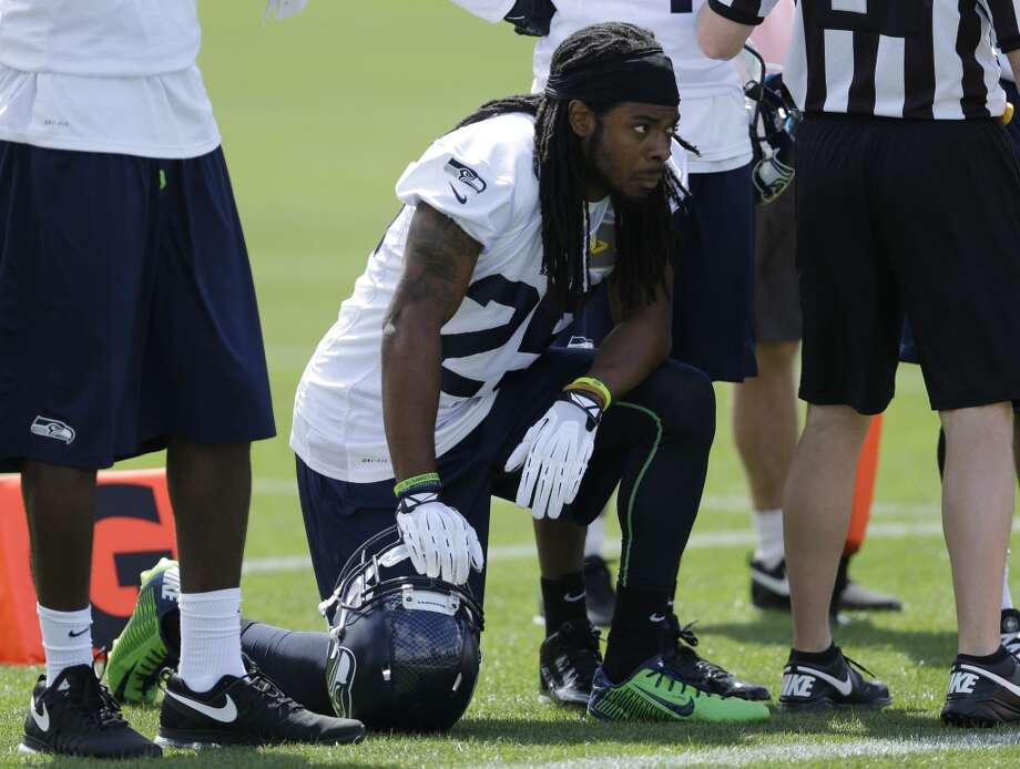 Seattle Seahawks cornerback Richard Sherman kneels on the sideline during Seahawks OTAs on Monday. Photo: Ted S. Warren, Associated Press