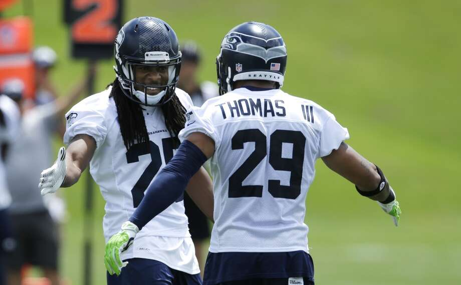 Seattle Seahawks cornerback Richard Sherman, left, reacts to a play with free safety Earl Thomas, right, during a practice drill at Seahawks OTAs on Monday. Photo: Ted S. Warren, Associated Press