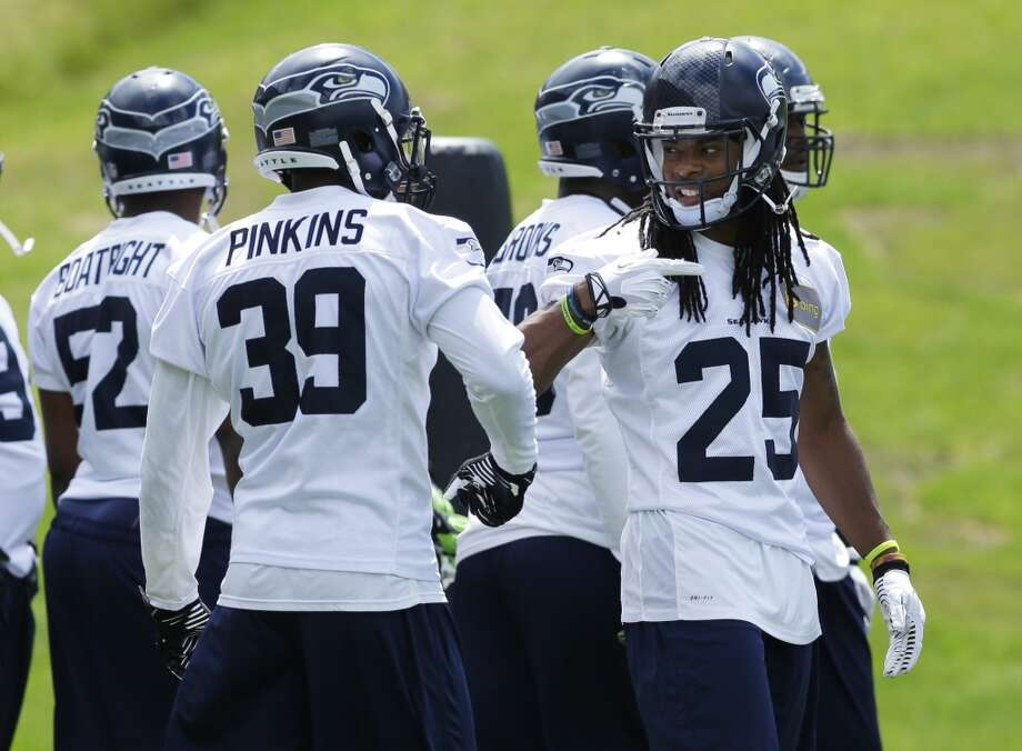 Seattle Seahawks cornerback Richard Sherman (25) talks with rookie cornerback Eric Pinkins (39) during Seahawks OTAs on Monday. Photo: Ted S. Warren, Associated Press