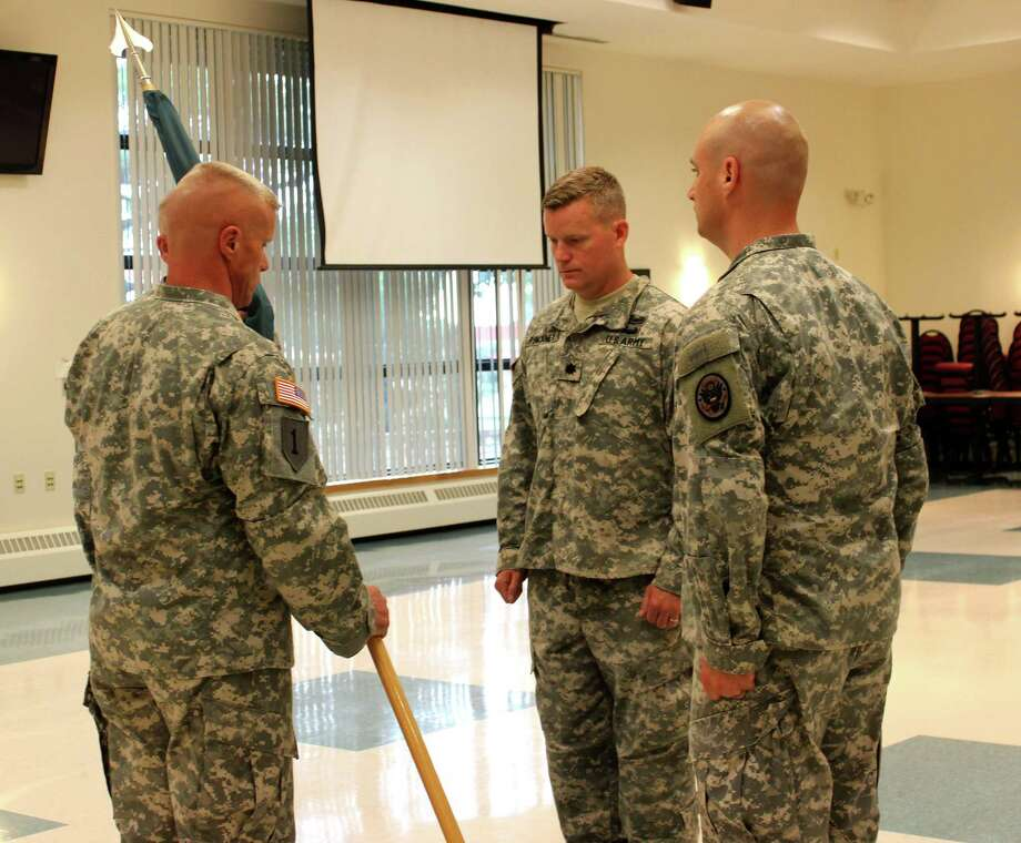 Lieutenant Colonel Thomas Benton, left, passes the guidon to Lieutenant Colonel Andrew Pinckney, center, as 1st Sgt. Noel Frederick, right, assists in the ceremony Monday afternoon, June 9, 2014, at Stratton Air National Guard base in Scotia N.Y. Lt. Col. Pinckney will take command of the New York National Guard's 2nd Weapons of Mass Destruction Civil Support Team (CST) from Lt. Col. Benton. (Selby Smith / Special to the Times Union) Photo: Selby Smith / 00027223A