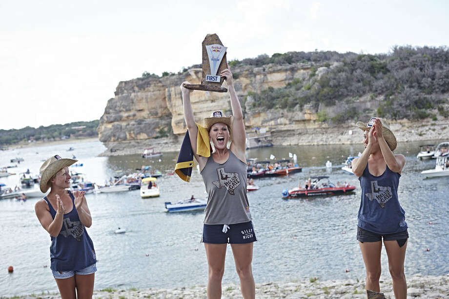 Cesilie Carlton and Rachelle Simpson of the USA celebrate with Anna Bader of Germany during the award ceremony of the second stop of the Red Bull Cliff Diving World Series at Possum Kingdom Lake, Texas, on June 7, 2014. Photo: Balazs Gardi, Courtesy Of Red Bull Cliff Diving / Balazs Gardi/Red Bull Cliff Diving