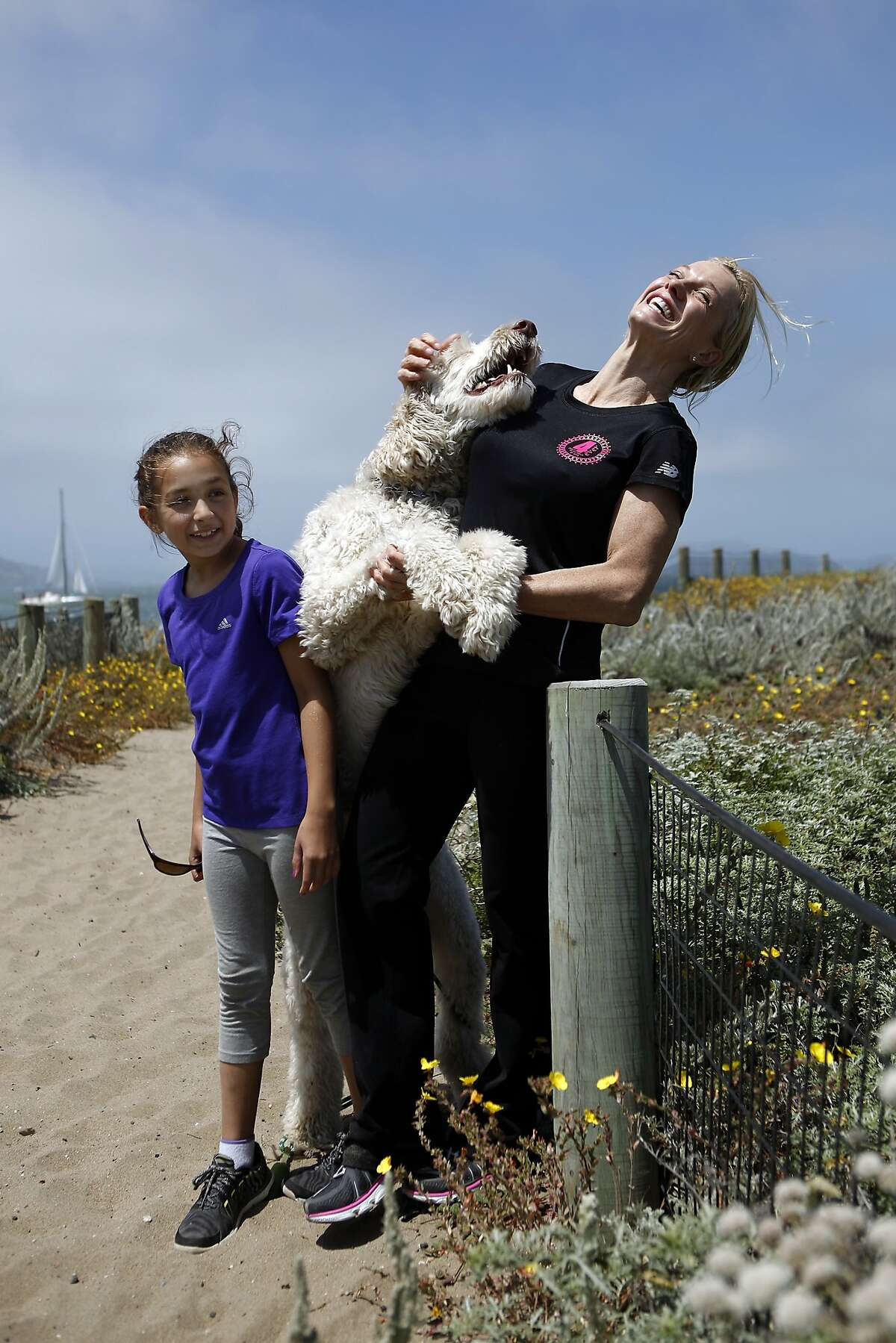 Dr. Pamela Munster, a UCSF breast cancer specialist diagnosed with breast cancer, poses for a portrait with her daughter Maya Daud, 10, and their dog Sampson at Crissy Field in San Francisco, CA, Saturday June 7, 2014.