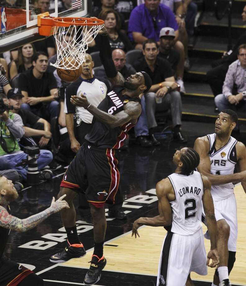 Miami Heat's LeBron James (06) dunks against Spurs' Kawhi Leonard (02) and Tim Duncan (21) in the first half of Game 2 of the 2014 NBA Finals at the AT&T Center on Sunday, June 8, 2014. Photo: Kin Man Hui, San Antonio Express-News