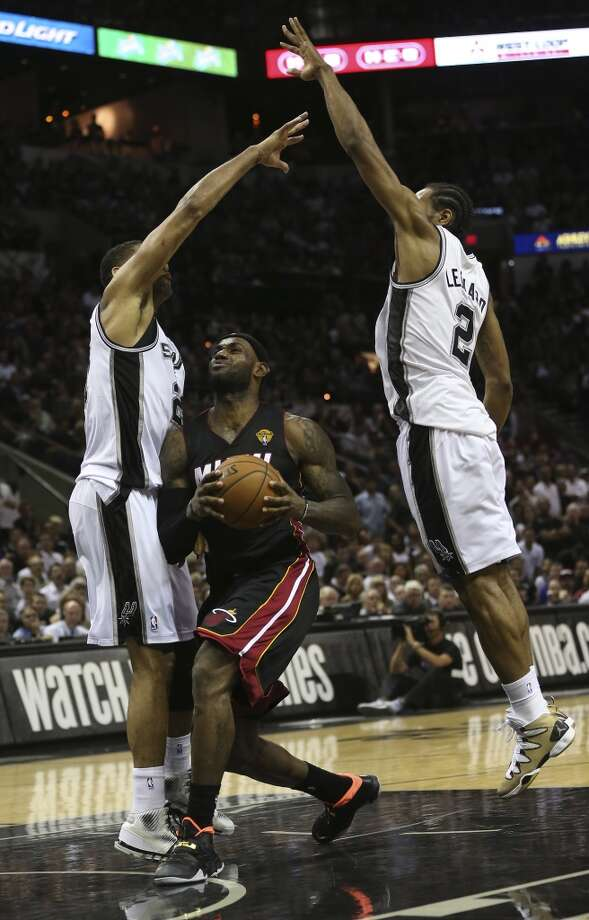 Miami Heat's LeBron James goes between San Antonio Spurs' Tim Duncan and Kawhi Leonard during the second half in game two of the NBA Finals at the AT&T Center, Sunday, June 8, 2014. The Heat won 98-96 to tie the series at 1-1. Photo: Jerry Lara, San Antonio Express-News