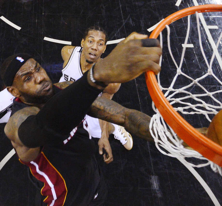 Heat forward LeBron James dunks in two of his game-high 35 points in Game 2 on Sunday as Kawhi Leonard watches. Leonard, who was a stalwart in last year's Finals, is off to a slow start. Photo: Larry W. Smith / Associated Press / EPA Pool