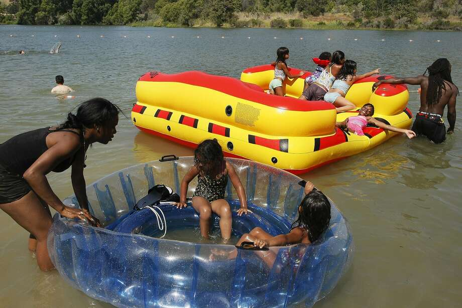 Diamond Fuller and her boyfriend Joe pull their kids and other lake-goers through Del Valle in Livermore, Calif. on Monday, June, 9, 2014. As temperatures soared people found ways to stay cool. Photo: James Tensuan, The Chronicle