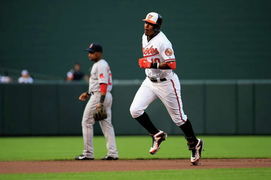BALTIMORE, MD - JUNE 09: Jonathan Herrera #10 of the Boston Red Sox looks on as Adam Jones #10 of the Baltimore Orioles rounds the bases after hitting a solo home run in the first inning at Oriole Park at Camden Yards on June 9, 2014 in Baltimore, Maryland.  (Photo by Rob Carr/Getty Images) ORG XMIT: 477584699 Photo: Rob Carr / 2014 Getty Images