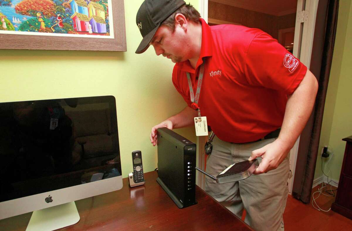 Comcast technician Thomas Cable installs a wireless gateway in a Houston home Monday. Comcast is turning home routers into public Wi-Fi hotspots.