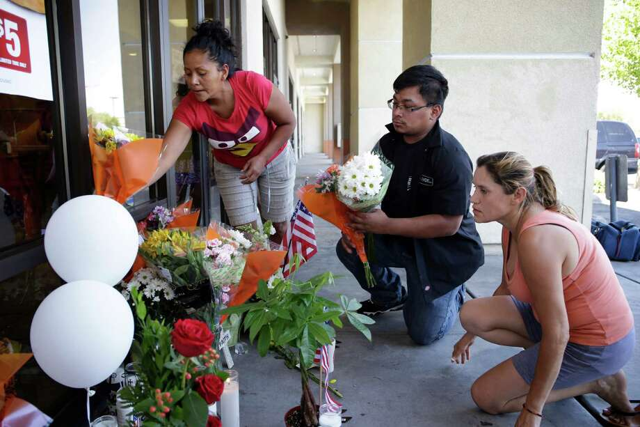 Sandra Flores, left, Jonathan Solano and Leticia Trejo place flowers at a CiCi's Pizza for a memorial to two Las Vegas Metropolitan Police officers who were killed. Photo: John Locher, STF / AP