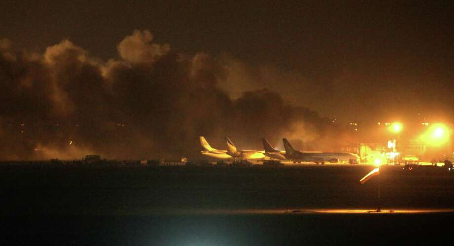 Fire illuminates the sky above the Jinnah International Airport in Karachi where security forces are fighting with attackers Sunday night, June 8, 2014, in Pakistan. Gunmen disguised as police guards attacked a terminal with machine guns and a rocket launcher during a five-hour siege that killed a number of people as explosions echoed into the night, while security forces retaliated and killed all the attackers, officials said Monday. (AP Photo/Fareed Khan) ORG XMIT: ISL112 Photo: Fareed Khan / AP