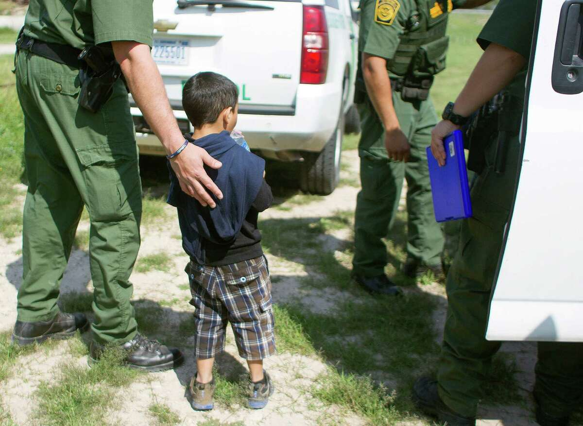 """Boarder Patrol agents escort a 4-year-old boy and his 17-year-old uncle (not pictured) from Honduras into a transport vehicle after the two crossed the Rio Grande from Mexico into Anzaldulas Park and turned themselves into a Hidalgo County Precinct 3 Constable Thursday, Feb. 20, 2014, in Mission. Anzaldulas Park is on the frontline of what federal officials have dubbed é¢Ã©""""éºthe surgeé¢Ã©""""é¹ é¢Ã©""""é a steep increase in the numbers of children caught crossing the border illegally and alone. Arrests have spiked from 8,000 in 2008 to more than 38,000 last year. ( Johnny Hanson / Houston Chronicle )"""
