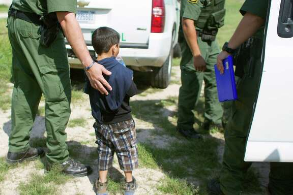 "Boarder Patrol agents escort a 4-year-old boy and his 17-year-old uncle (not pictured) from Honduras into a transport vehicle after the two crossed the Rio Grande from Mexico into Anzaldulas Park and turned themselves into a Hidalgo County Precinct 3 Constable Thursday, Feb. 20, 2014, in Mission. Anzaldulas Park is on the frontline of what federal officials have dubbed é¢Ã©""éºthe surgeé¢Ã©""é¹ é¢Ã©""é a steep increase in the numbers of children caught crossing the border illegally and alone. Arrests have spiked from 8,000 in 2008 to more than 38,000 last year. ( Johnny Hanson / Houston Chronicle )"