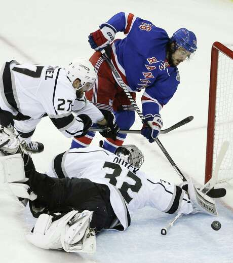 Los Angeles goalie Jonathan Quick blocks a shot by New York Rangers right winger Mats Zuccarello (right) as Kings defenseman Alec Martinez helps out in the first period of Game 3. Photo: Frank Franklin II / Associated Press / AP