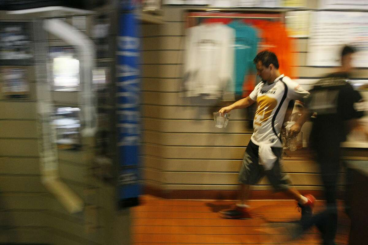 Hodan Ramirez runs glasses back to the kitchen at Double D's in Los Gatos, Calif. on Friday, May 30, 2014. The manager says downtown Los Gatos was filled with people when Brazil went to the 1994 World Cup.